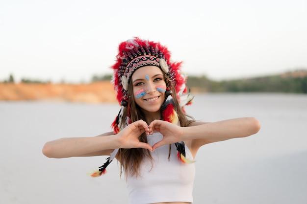 Linda jovem caucasiana em um top branco na cabeça está usando um chapéu indiano roach permanente no deserto.