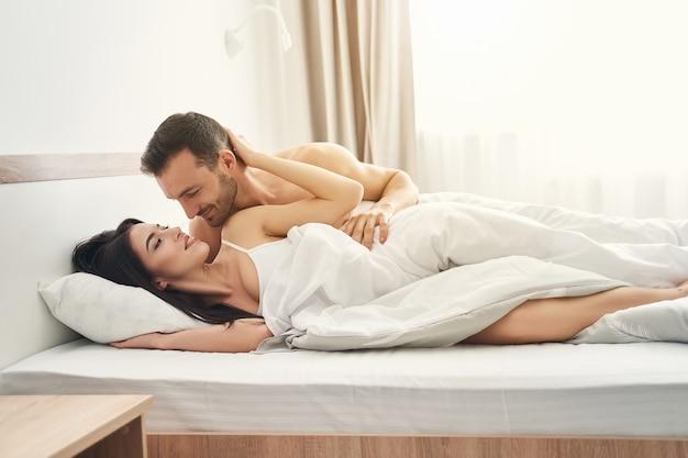 Linda jovem caucasiana feliz e seu marido afetuoso olhando um para o outro na cama