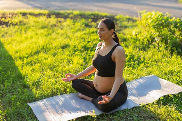 Linda jovem caucasiana grávida está meditando enquanto está sentada em um tapete no gramado em um dia ensolarado