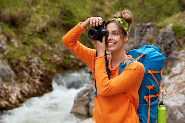 Linda jovem caucasiana tira fotos com uma câmera moderna, usa bandana e macacão laranja