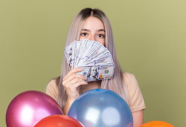 Linda jovem coberta com dinheiro em pé atrás de balões isolados na parede verde oliva