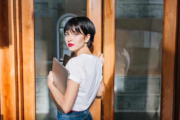 Linda jovem com cabelo escuro e brilhante abrindo a porta de vidro carregando um computador