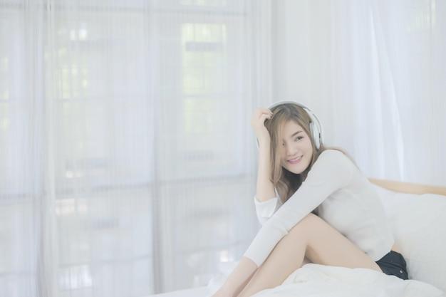 Linda jovem com cabelos loiros ouve música em casa. feche acima da senhora feliz no quarto