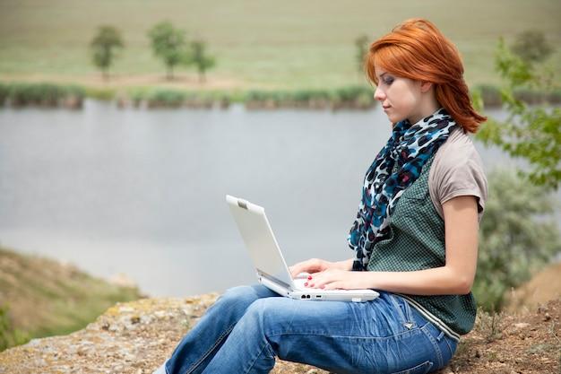 Linda jovem com laptop na rocha perto de lago e árvore.