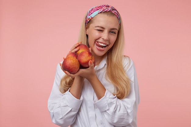Linda jovem com longos cabelos loiros se divertindo, piscando e puxando a língua com um largo sorriso, vestindo roupas casuais