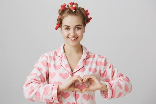 Linda jovem com rolos de cabelo e pijamas mostrando o sinal do coração