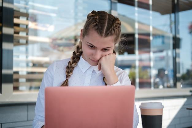 Linda jovem com um laptop em uma mesa em um café de verão