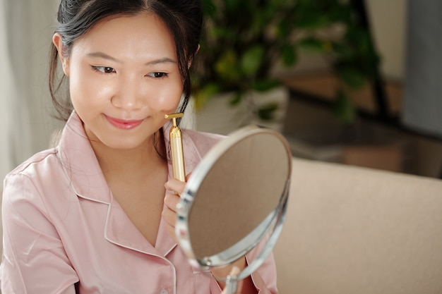 Linda jovem com uma pele perfeita e impecável, olhando no espelho e massageando o rosto com o rolo na ...