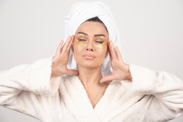 Linda jovem com uma toalha na cabeça e um manto branco usando adesivos sob os olhos