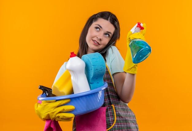 Linda jovem de avental e luvas de borracha segurando a bacia com ferramentas de limpeza e spray de limpeza olhando para cima sorrindo com uma carinha feliz