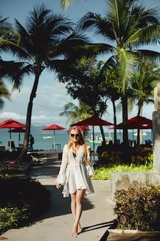 Linda jovem de biquíni posando sob as palmeiras no território de um resort luxuoso na ...