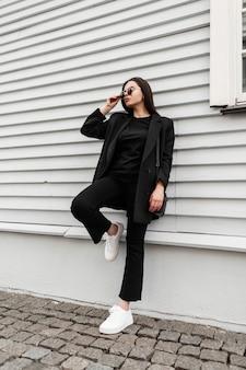 Linda jovem de blazer em t-shirt jeans em sapatos de ginástica com bolsa em óculos de sol está descansando perto de prédio de madeira vintage na rua. linda garota com roupa jovem casual na moda ao ar livre