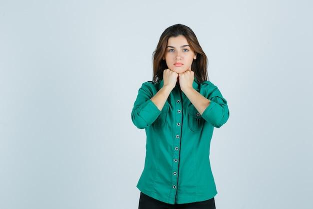 Linda jovem de camisa verde, mantendo os punhos sob o queixo e parecendo chateada, vista frontal.