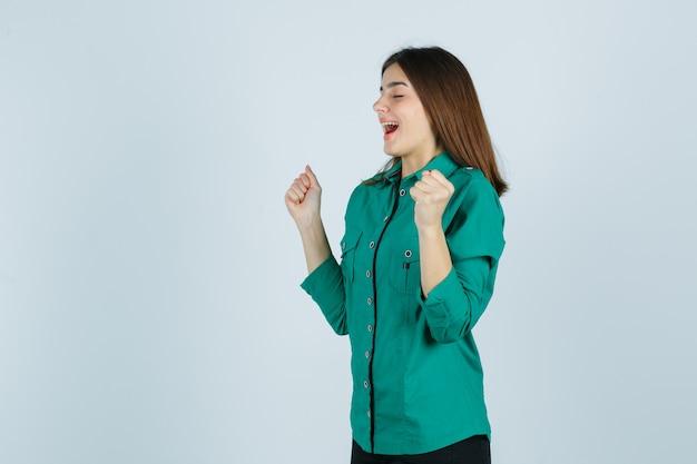 Linda jovem de camisa verde, mostrando o gesto do vencedor e olhando feliz, vista frontal.