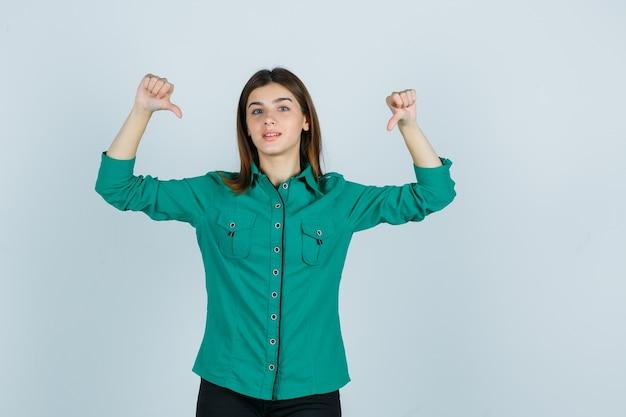 Linda jovem de camisa verde, mostrando os polegares duplos para baixo e parecendo decepcionada, vista frontal.