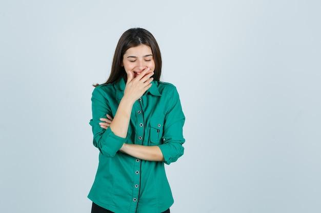Linda jovem de camisa verde, segurando a mão na boca e olhando feliz, vista frontal.