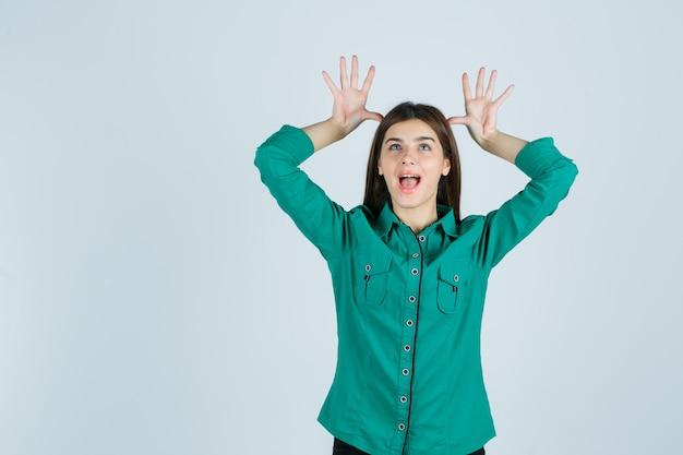 Linda jovem de camisa verde, segurando as mãos na cabeça como orelhas e olhando engraçado, vista frontal.