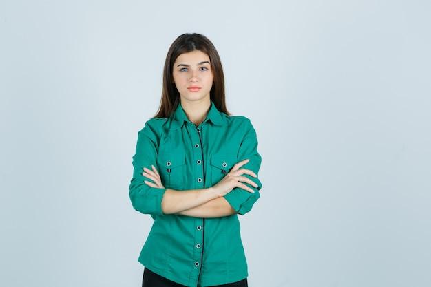Linda jovem de camisa verde, segurando os braços cruzados e olhando séria, vista frontal.