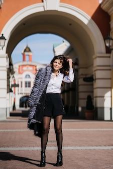 Linda jovem de casaco de pele, saia branca e camisa preta na cidade.