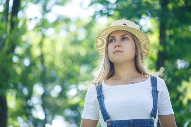 Linda jovem de macacão jeans e um chapéu leve caminhando no parque