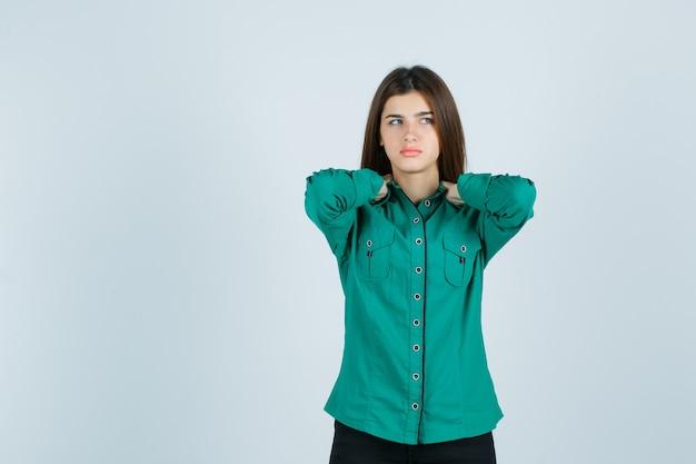 Linda jovem de mãos dadas no pescoço em uma camisa verde e olhando para baixo, vista frontal.