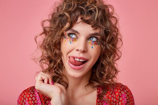 Linda jovem de olhos azuis, cabelo castanho cacheado e maquiagem festiva, posando com um top colorido e enfeitado, olhando para o lado com alegria e mostrando a língua