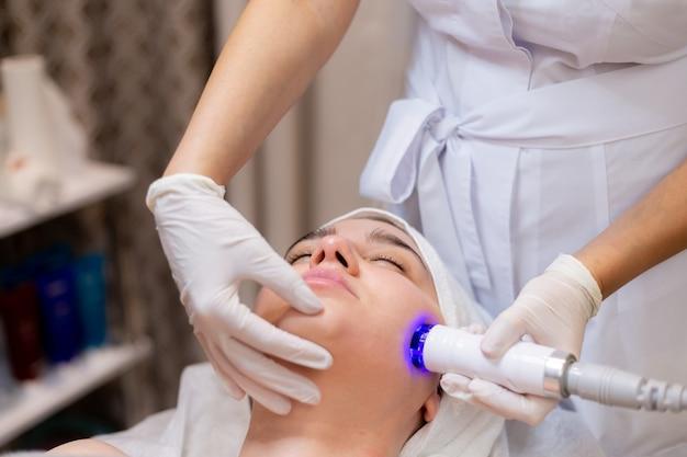 Linda jovem deita-se na mesa da esteticista e recebe procedimentos com aparelho profissional para rejuvenescimento e hidratação da pele