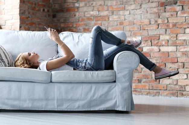Linda jovem descansando no sofá, sala interior