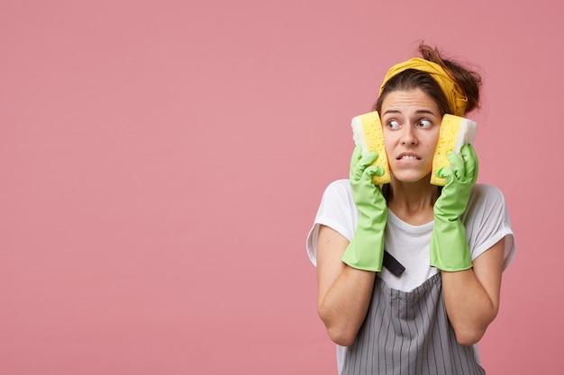 Linda jovem dona de casa olhando para o lado com uma expressão assustada e aterrorizada, segurando esponjas nas bochechas, sentindo-se frustrada por ter que limpar todo o apartamento sujo sozinha