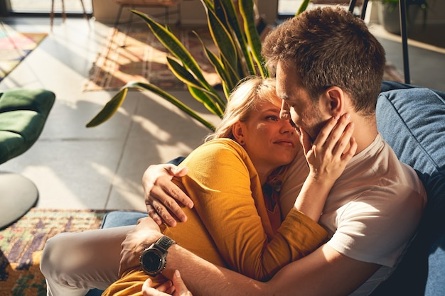 Linda jovem e amorosa mulher caucasiana casada olhando com ternura para o marido adormecido no sofá