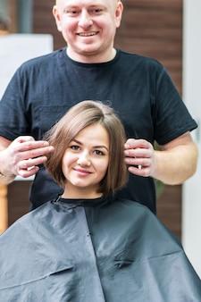 Linda jovem e seu cabeleireiro sorrindo olhando no espelho no salão de cabeleireiro.