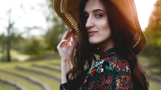Linda jovem em brilho através do vestido toque chapéu de palha. garota caminhando na encosta como cultivo de arroz