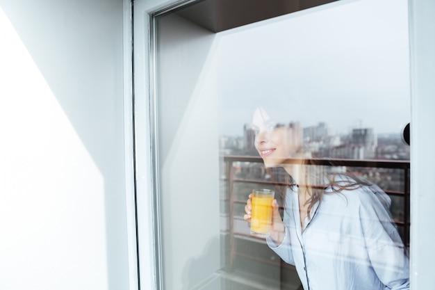 Linda jovem em casa olhando pela janela bebendo suco