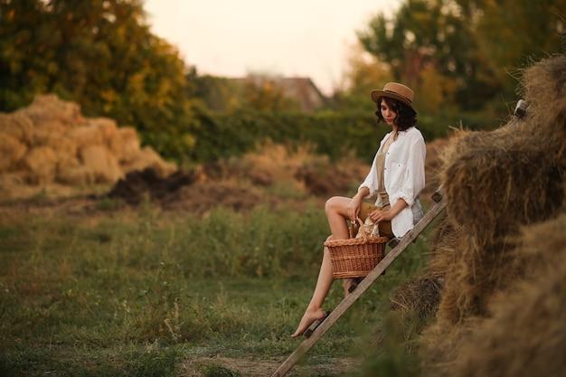 Linda jovem em estilo rústico sentada descansando no campo em uma velha escada de madeira