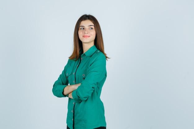 Linda jovem em pé com os braços cruzados, olhando para longe na camisa verde e olhando alegre, vista frontal.