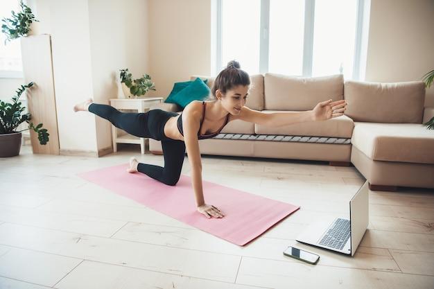 Linda jovem em roupas esportivas fazendo exercícios em casa no chão, olhando o tutorial no laptop