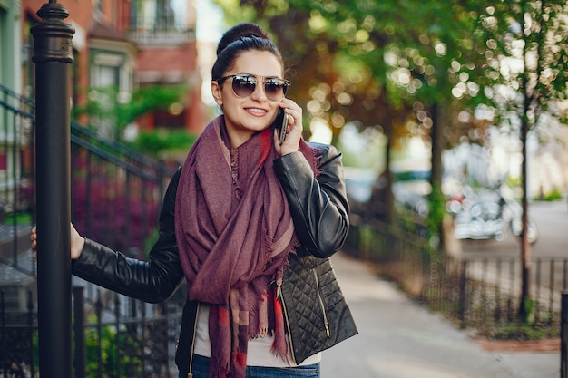 Linda jovem em sua casa e usa um telefone