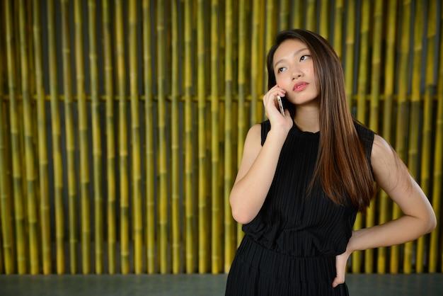 Linda jovem empresária asiática falando ao telefone contra uma cerca de bambu