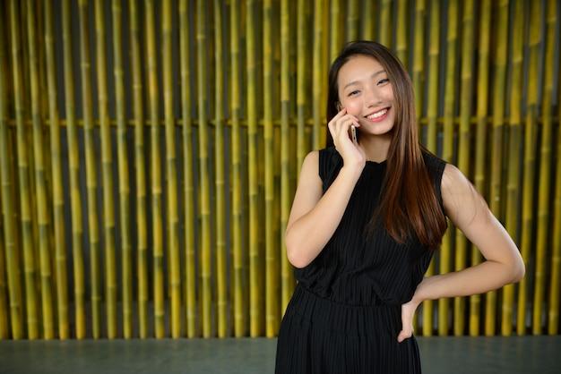 Linda jovem empresária asiática feliz falando ao telefone contra uma cerca de bambu
