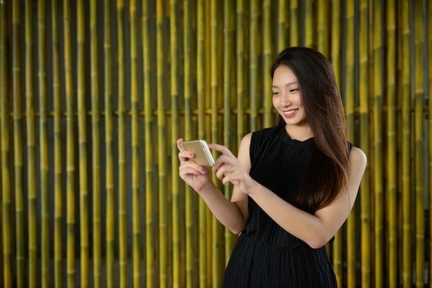 Linda jovem empresária asiática feliz usando o telefone contra uma cerca de bambu