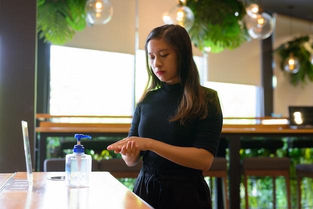 Linda jovem empresária asiática usando desinfetante para as mãos como etiqueta de higiene adequada no café