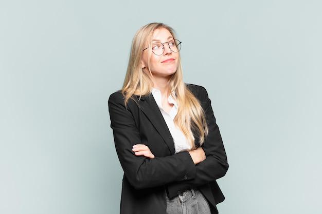 Linda jovem empresária encolhendo os ombros, sentindo-se confusa e insegura, duvidando com os braços cruzados e olhar perplexo