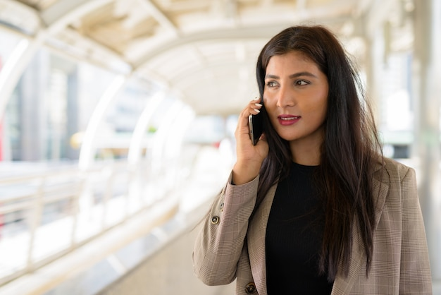 Linda jovem empresária indiana feliz falando ao telefone na passarela da cidade