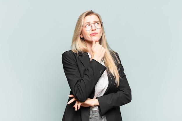 Linda jovem empresária pensando, se sentindo duvidosa e confusa, com diferentes opções, imaginando qual decisão tomar