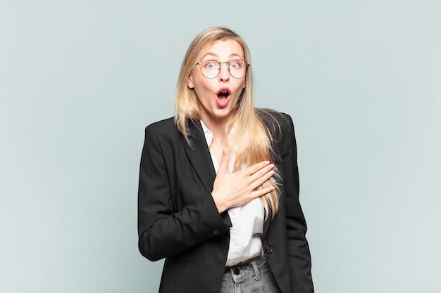 Linda jovem empresária se sentindo chocada e surpresa, sorrindo, levando a mão ao coração, feliz por ser a única ou demonstrando gratidão