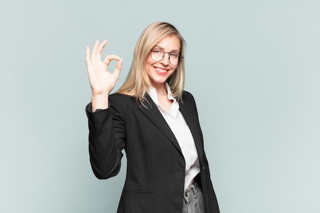 Linda jovem empresária se sentindo feliz, relaxada e satisfeita, mostrando aprovação com um gesto de ok, sorrindo