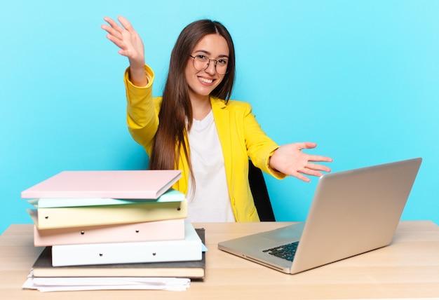 Linda jovem empresária sorrindo alegremente dando um abraço caloroso, amigável e afetuoso de boas-vindas, sentindo-se feliz e adorável