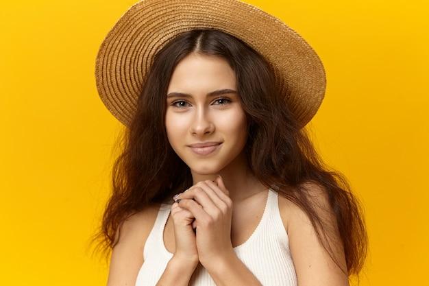 Linda jovem encantadora com pele bronzeada, maquiagem natural e cabelo solto posando em estúdio