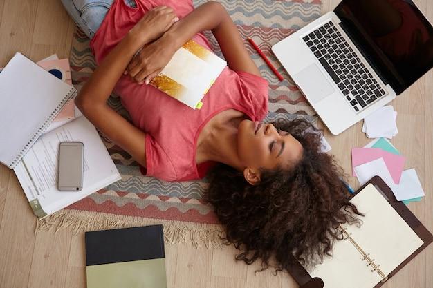 Linda jovem encaracolada com pele escura deitada no chão entre livros, cadernos e laptop, posando sobre um tapete colorido com os olhos fechados e um sorriso agradável