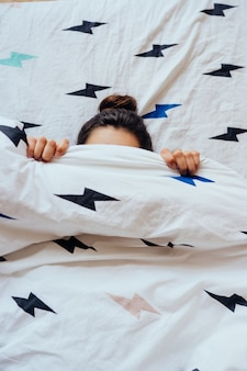 Linda jovem encontra-se na cama coberta com manta